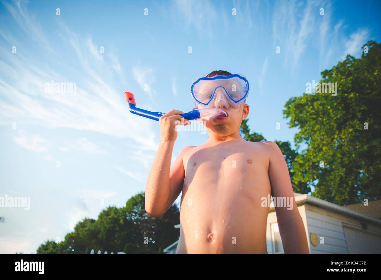 Un niño lleva una máscara de buceo contra un cielo azul con pocas nubes. Imagen De Stock