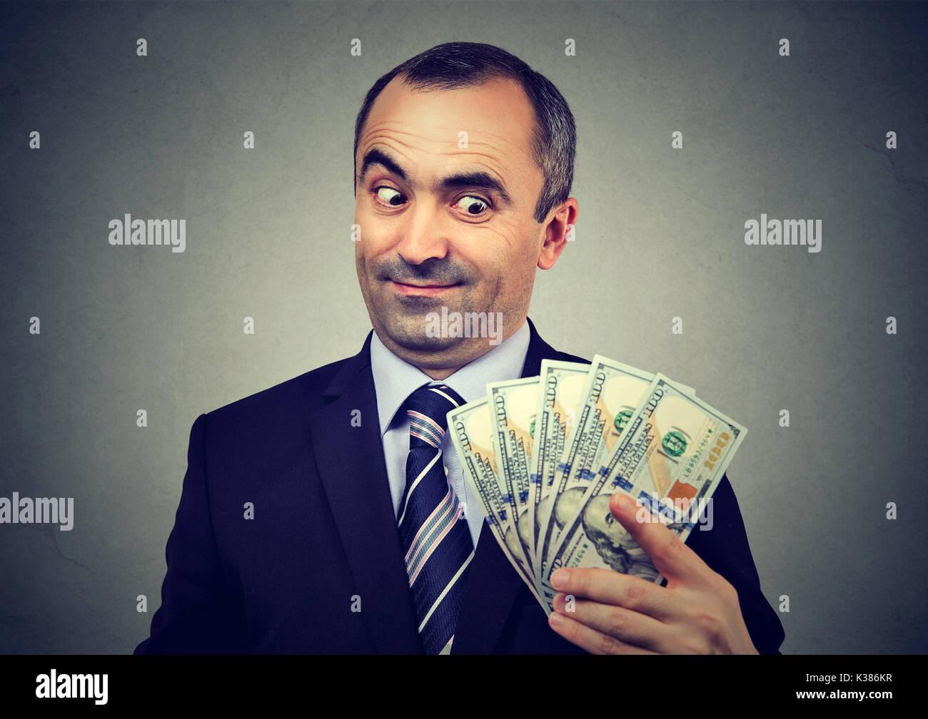 Gracioso astuto hombre de negocios mantiene mirando dinero Imagen De Stock