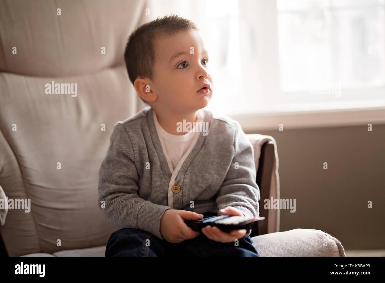 d9aa56294 Chico está viendo la televisión mientras está sentado en un sofá Imagen De  Stock