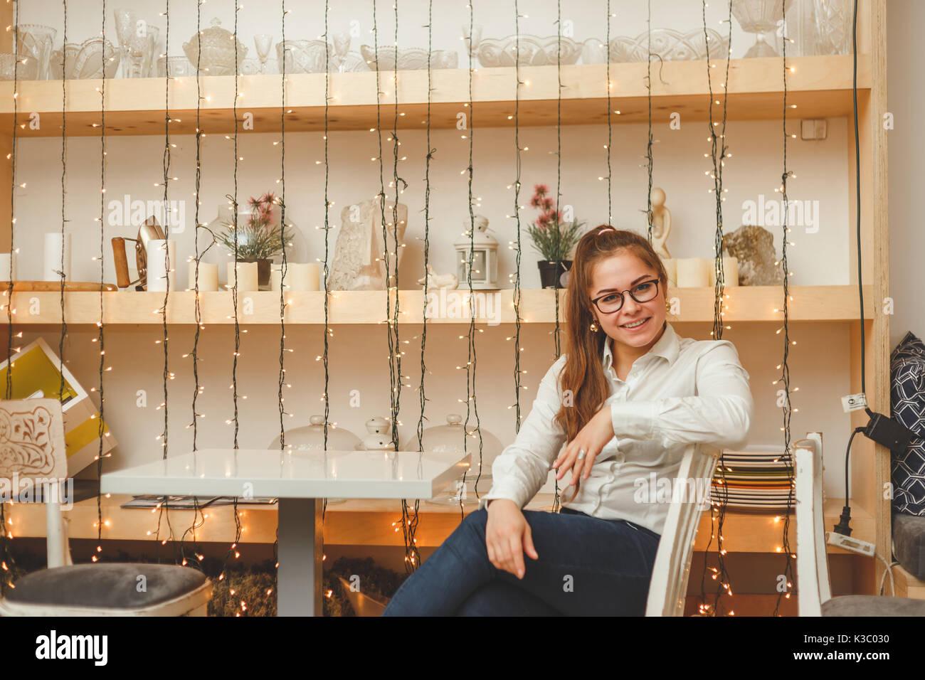 Empresa joven mujer sentada a la mesa en su café. Imagen De Stock