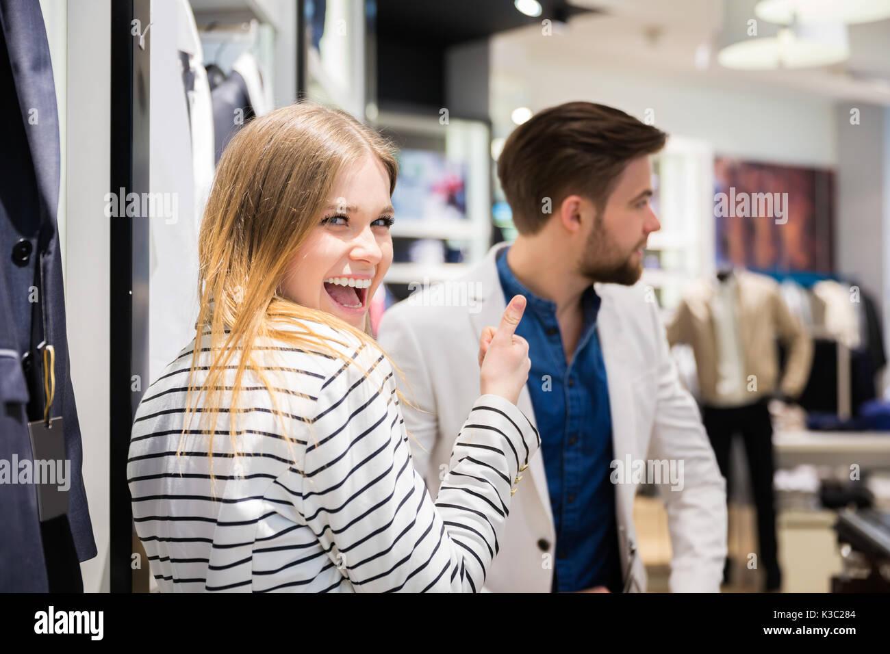 Una foto de la joven pareja en la boutique. La chica simplemente recogió una chaqueta de su novio. Imagen De Stock