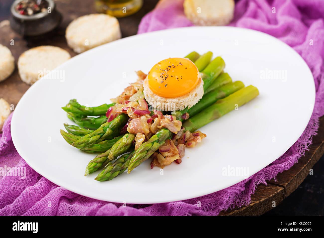 Los retoños de espárragos con jamón y la yema de huevo de gallina en tostadas Foto de stock