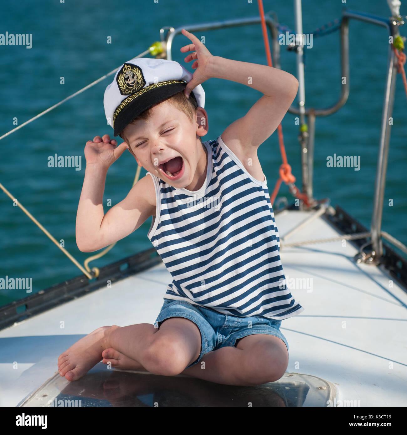 Funny little boy vistiendo captain hat sentado a bordo de la embarcación de  lujo con agua 2f6e6c31ae7