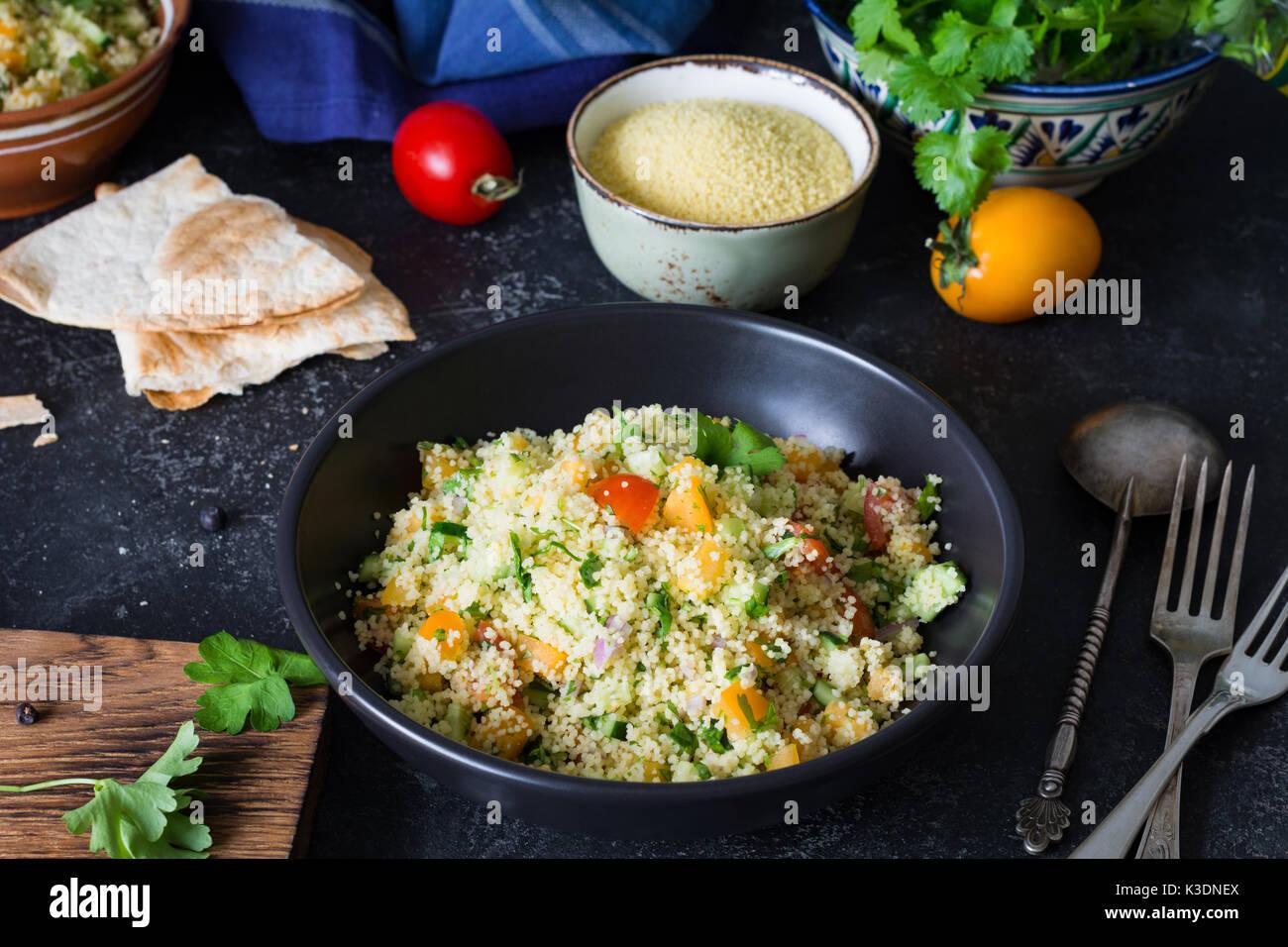 Cocina árabe libanés: deliciosa ensalada saludable con cous cous, vegetales frescos y verdes llamados tabbouleh tazón negro cocina auténtica. Imagen De Stock