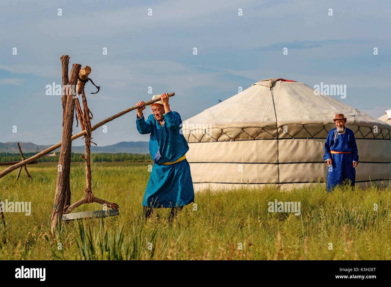 Mongolia interior, China-July 26, 2017: tradicionalmente vestidos viejos hombres mongol procesar las pieles de oveja Foto de stock