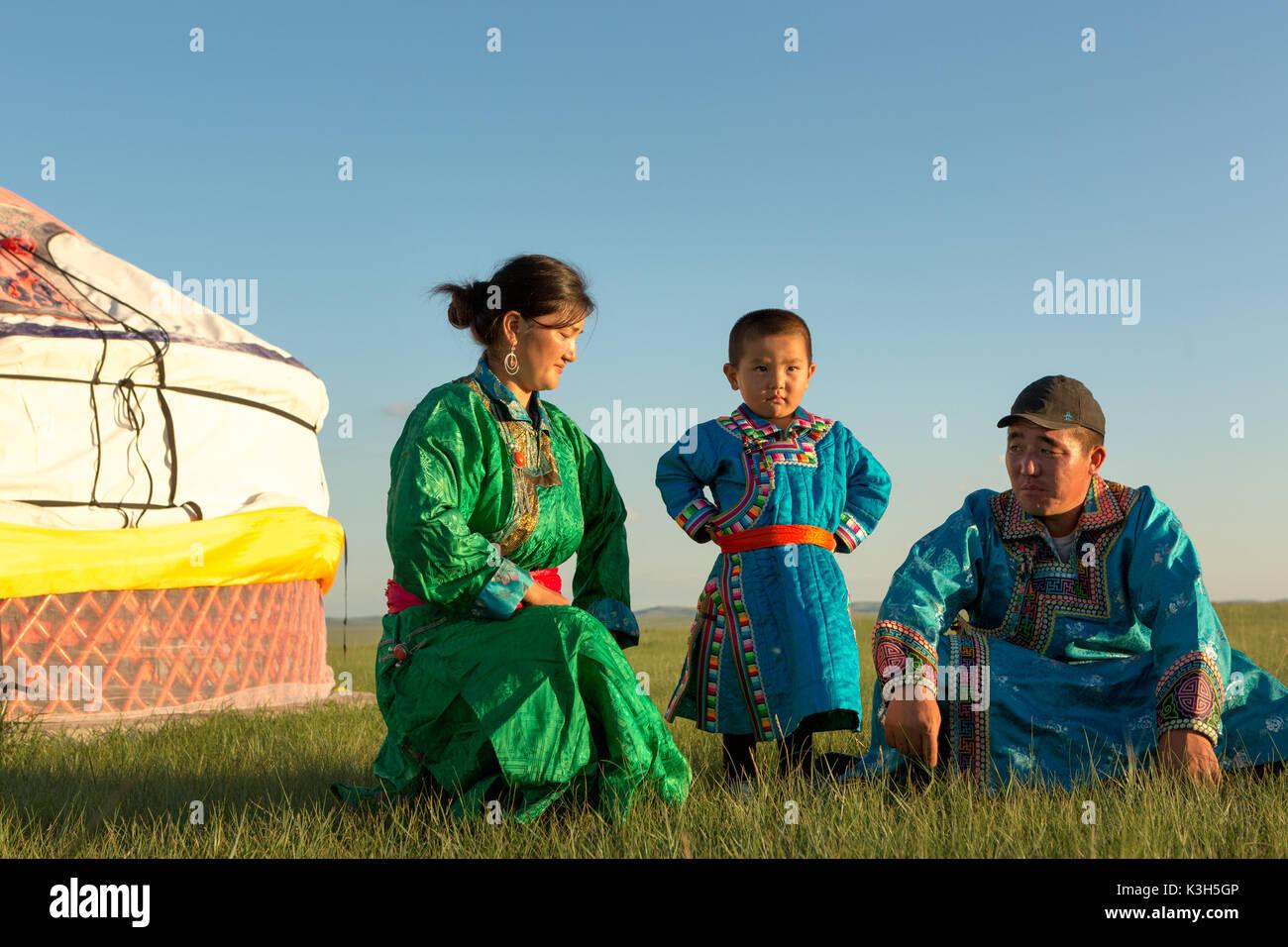 Mongolia interior, China-Julio 30, 2017: familia mongólica nómadas con sus coloridos vestidos tradicionales cerca de su yurt en inmensas praderas del país Imagen De Stock
