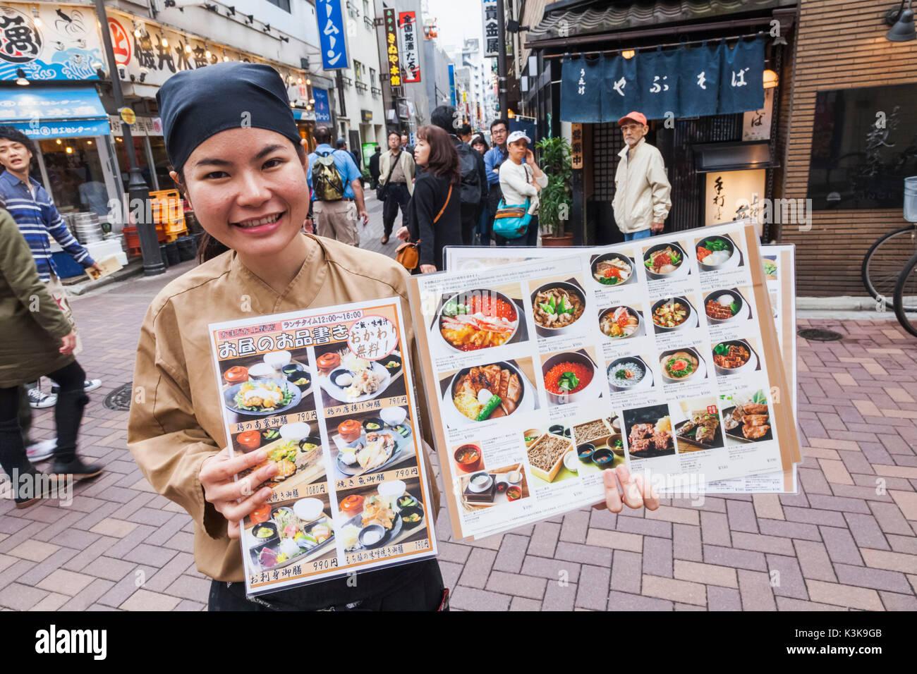 Japón, Hoshu, Tokio, Ueno, calle comercial Ameyoko, Chica sujetando el menú del restaurante Imagen De Stock