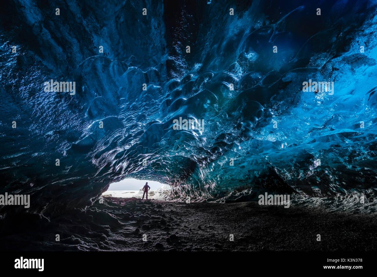 Hombre dentro de un hielo caver bajo el glaciar Vatnajokull, el Parque Nacional Vatnajokull, el este de Islandia, Islandia (MR) Imagen De Stock