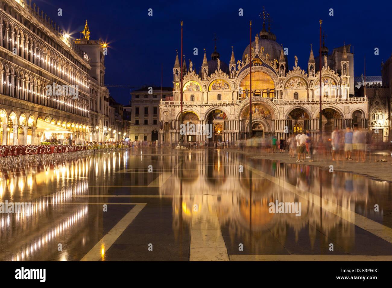 La Basílica de San Marcos de noche iluminado durante la hora azul se reflejan en las quietas aguas de acqua alta en Piazza San Marco, Venecia, Véneto, Italia con Imagen De Stock