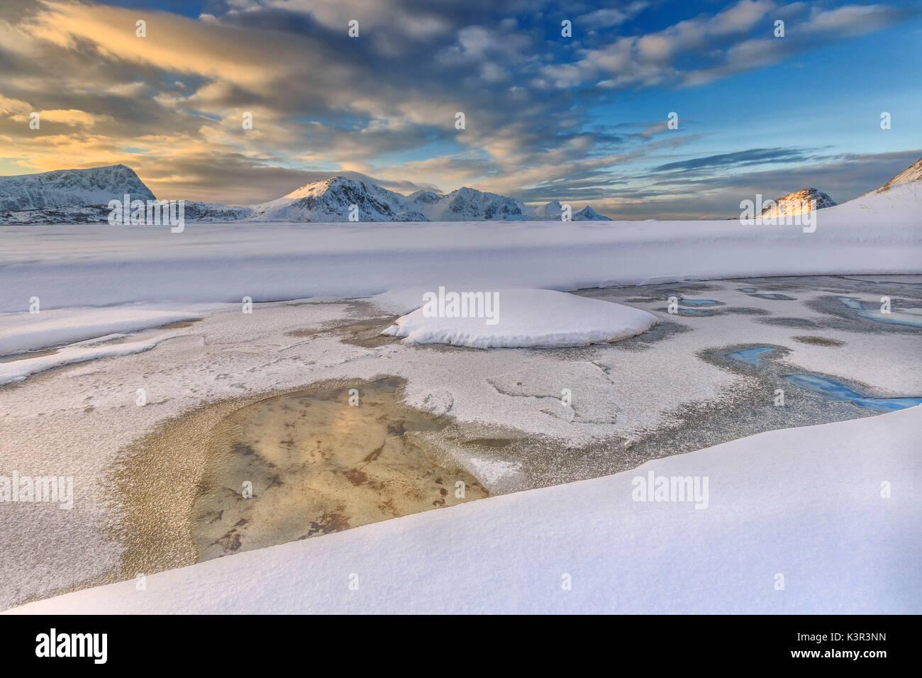 El amanecer dorado se refleja en una piscina de aguas cristalinas donde la nieve es casi derretido. Las Islas Lofoten Noruega Europa Haukland Foto de stock