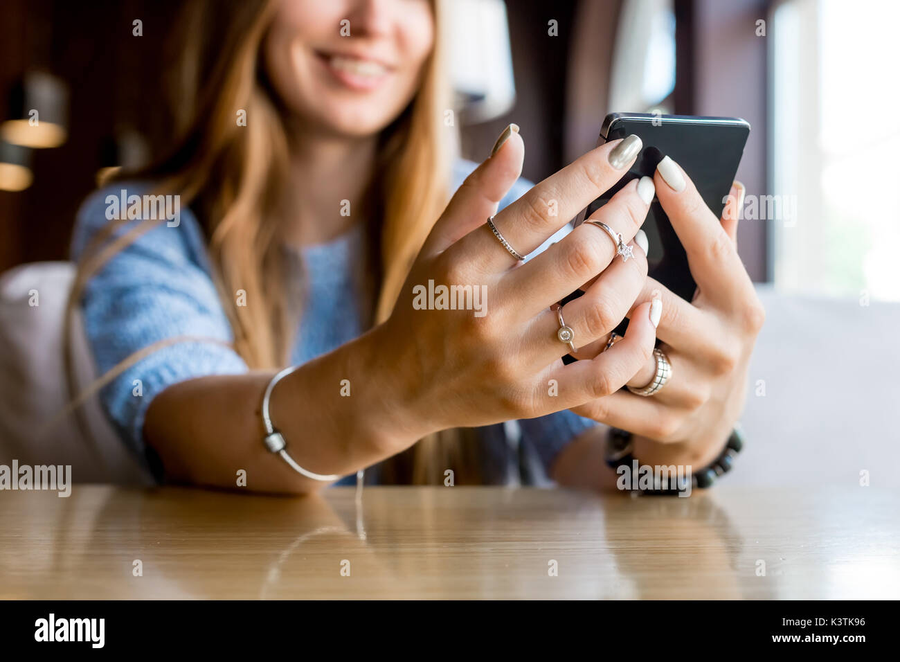 Cerca de manos de mujer locutorio telefónico con copia en blanco el espacio scree de su publicidad un mensaje de texto o contenido promocional, hipster chica viendo vídeos en el teléfono móvil durante la pausa para el café. Tonificado. El enfoque selectivo. Imagen De Stock