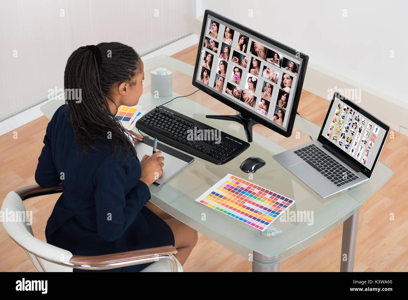 Diseñador de jóvenes africanos retoque fotos en el equipo Foto de stock