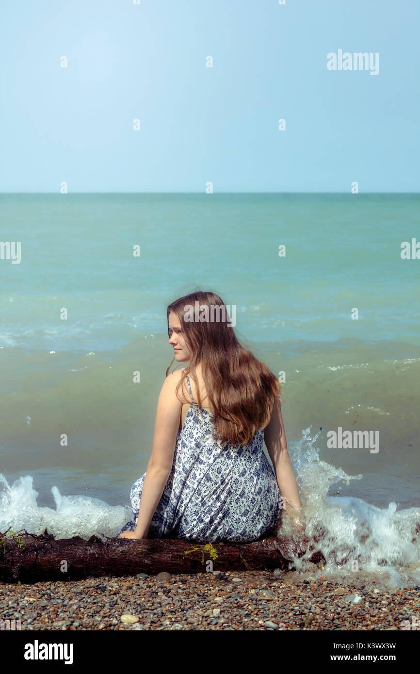 Una chica sentada en un registro en un lago Foto de stock