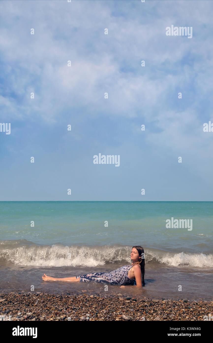 Una niña recostada en un lago en las ondas Foto de stock