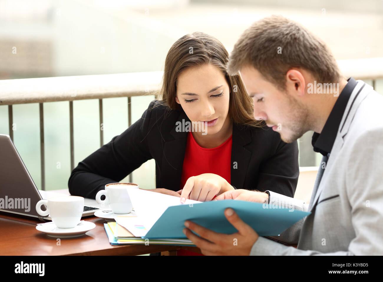 Dos ejecutivos coworking analizando documentos sentado en un bar. Imagen De Stock