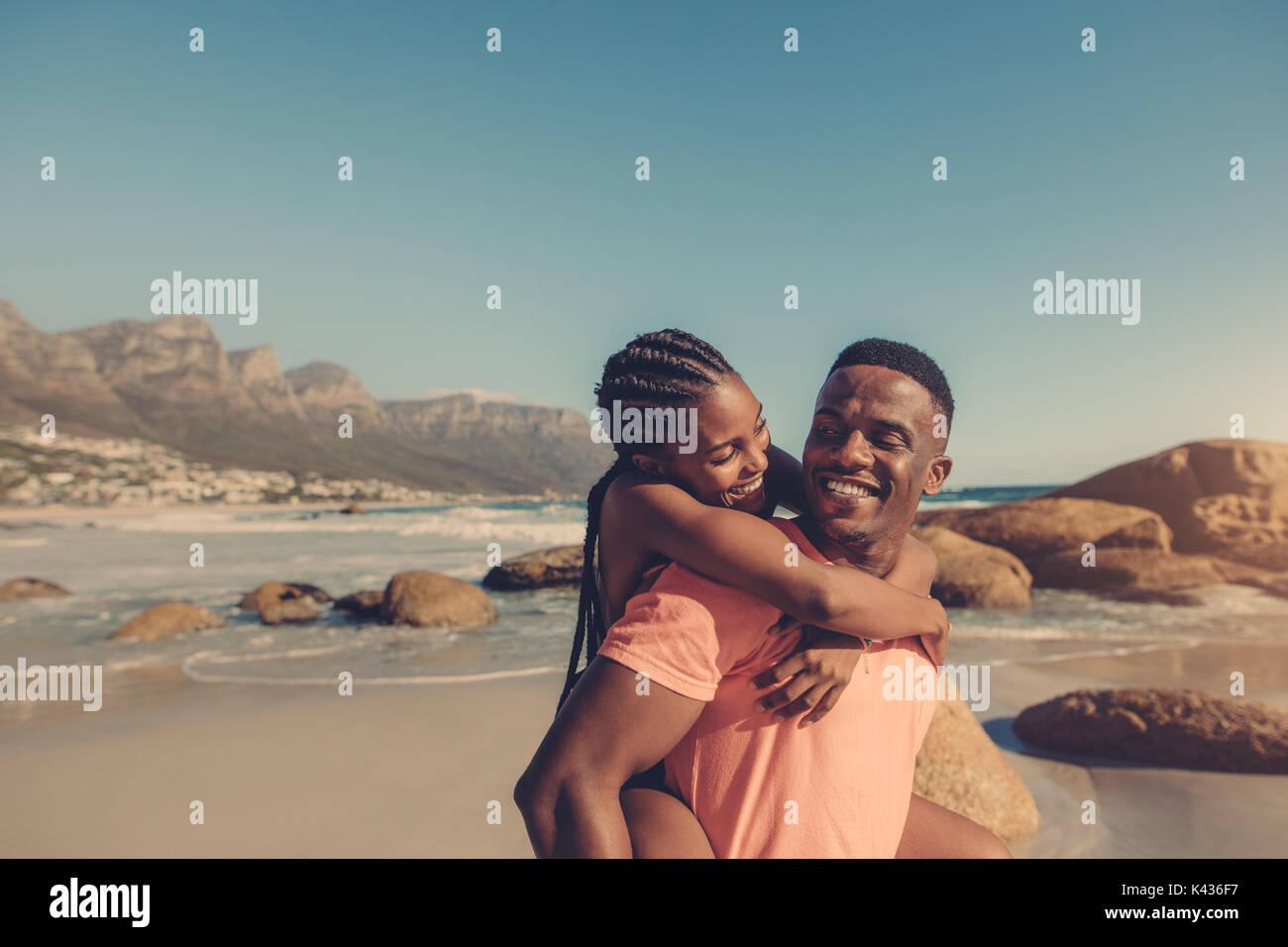Apuesto hombre africano dando piggyback paseo a su novia sonriente en la playa. Pareja divirtiéndose en la orilla del mar. Imagen De Stock