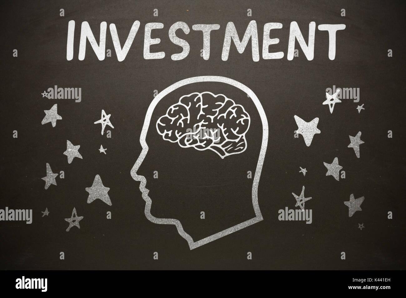 Imagen gráfica de cabeza humana con el cerebro en medio de formas de estrella a continuación texto de inversión contra la pizarra Imagen De Stock