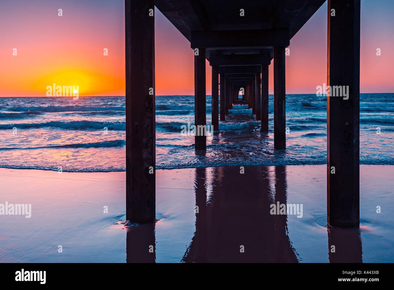 Puesta de sol vista desde debajo de embarcadero de Brighton, Australia del Sur Imagen De Stock