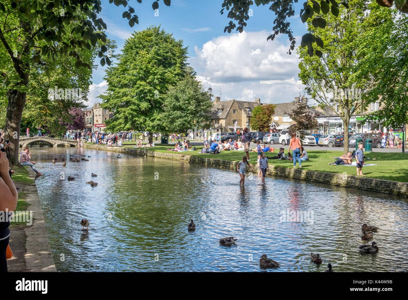 Vistas sobre el río Windrush muestra a los visitantes disfrutar del sol del verano en la línea verde en el centro Foto de stock