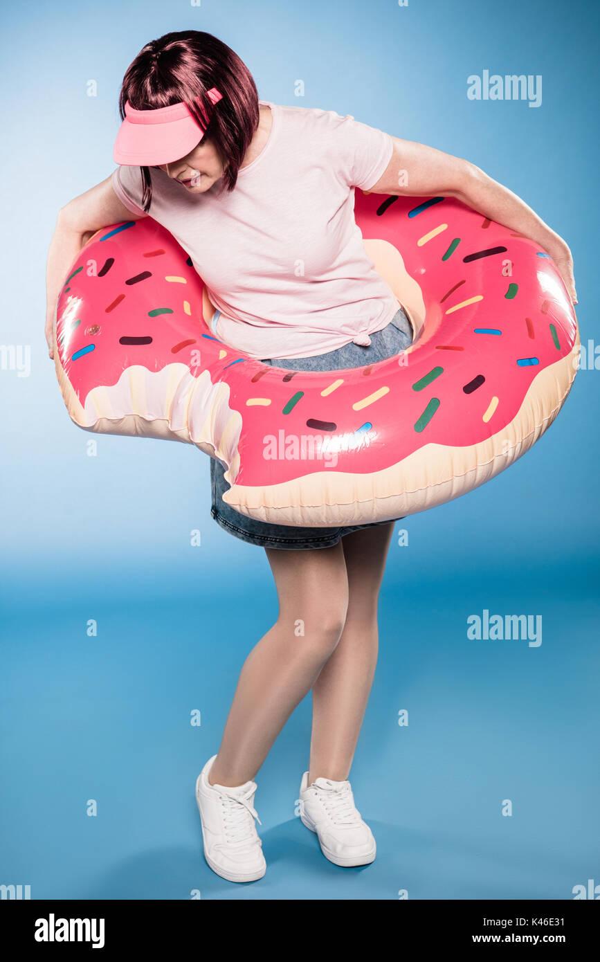 Elegante Mujer de pie con la natación tubo en forma de rosquilla Imagen De Stock