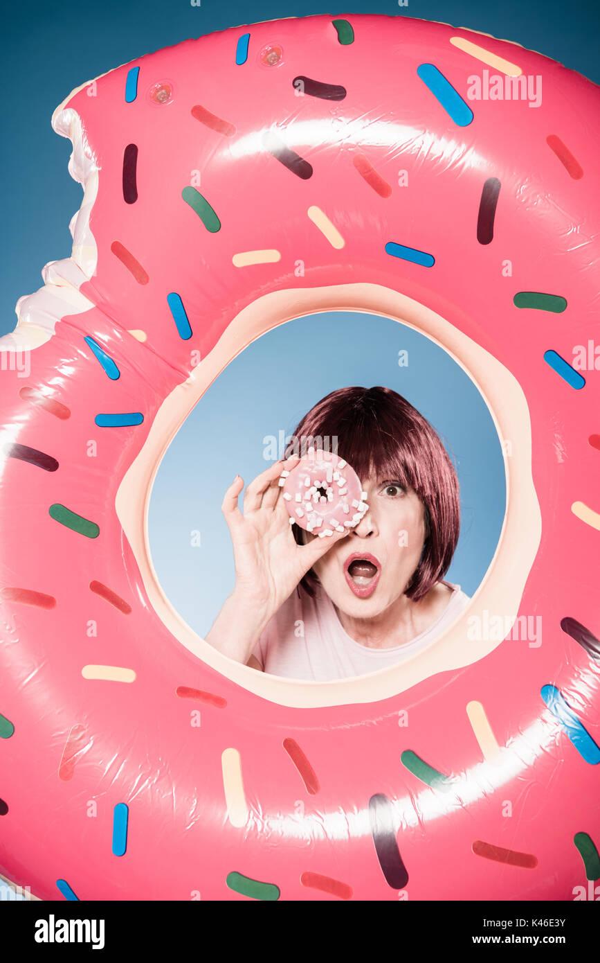 Mujer con una expresión facial celebración donut delante del ojo en tubo de natación Imagen De Stock