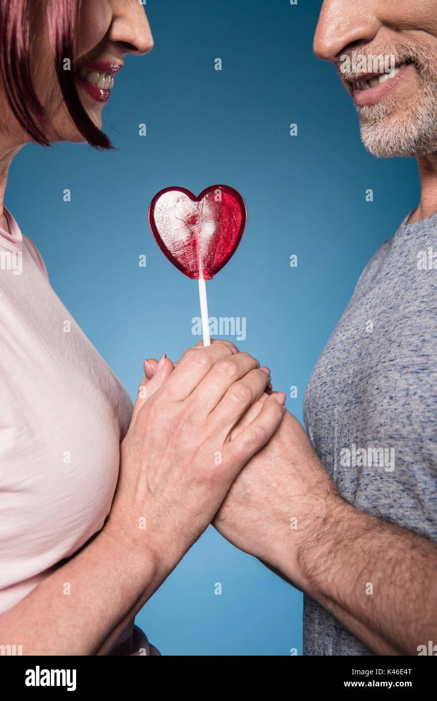 Captura recortada de la pareja de ancianos tomados de la mano con la piruleta en forma de corazón Foto de stock