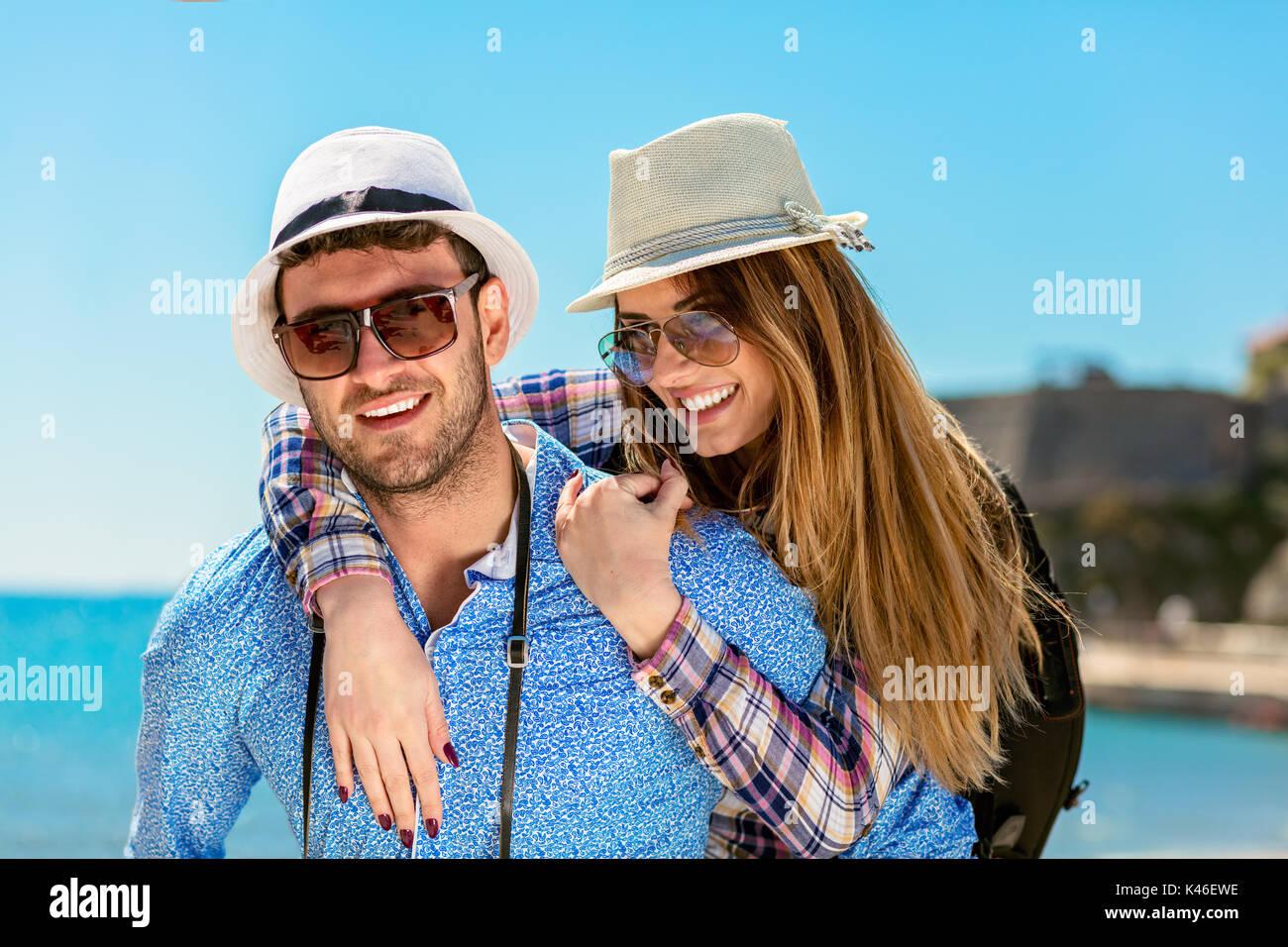 Feliz el hombre lleva a su novia en un viaje combinado ambas sonriendo y mirando muy felices disfrutando de sus vacaciones Imagen De Stock