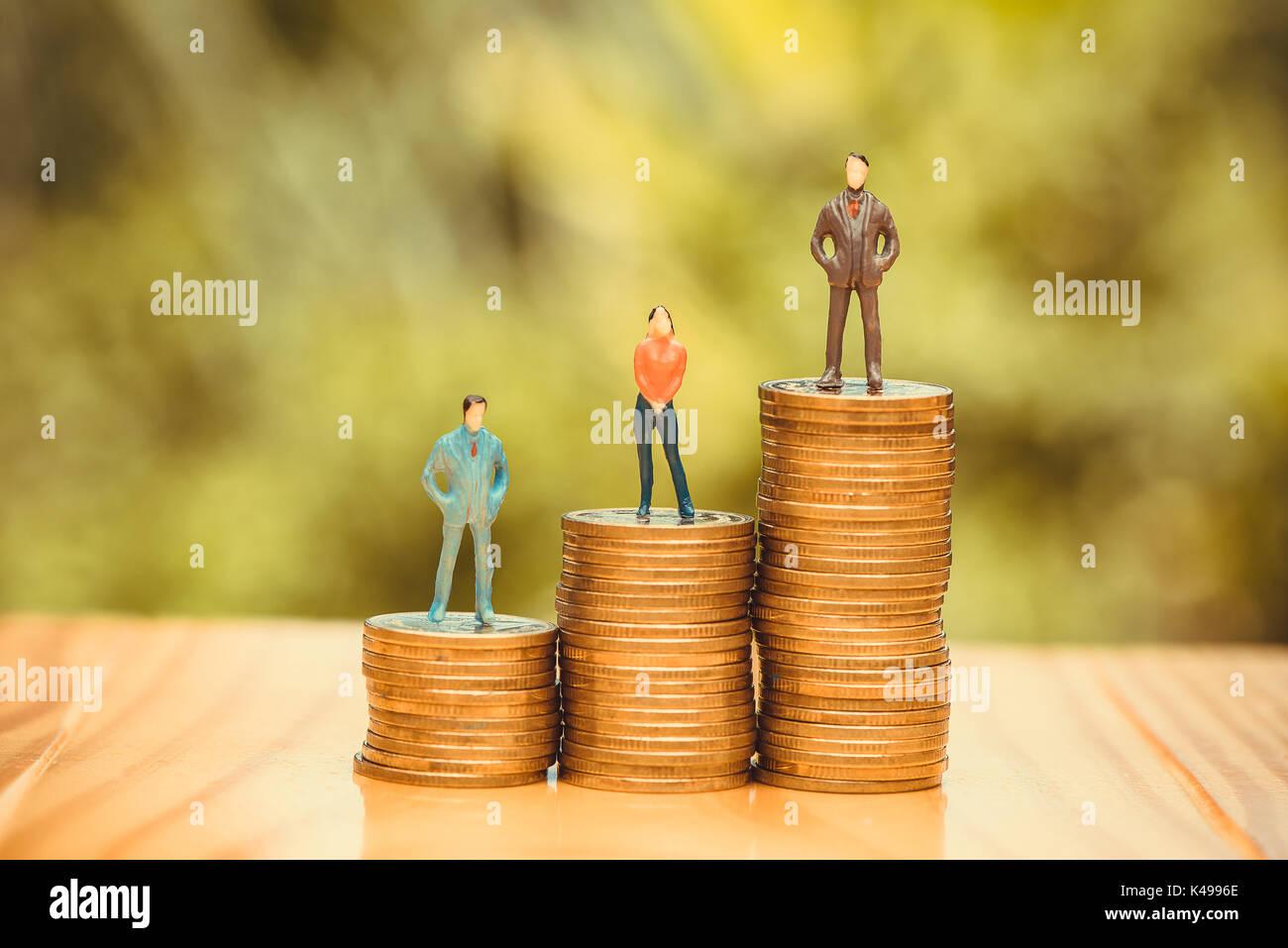 Pueblo en miniatura, pequeñas figuras de empresarios y de la mujer en la parte superior de las monedas. Dinero y financieros, el crecimiento empresarial concepto enfoque superficial en tonos suaves. Imagen De Stock