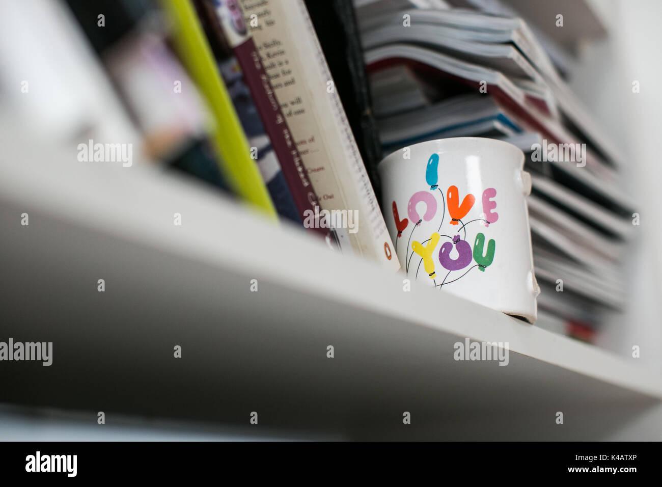 Una taza con un asa rota y mensaje sentimental en un estante en una casa de familia Foto de stock