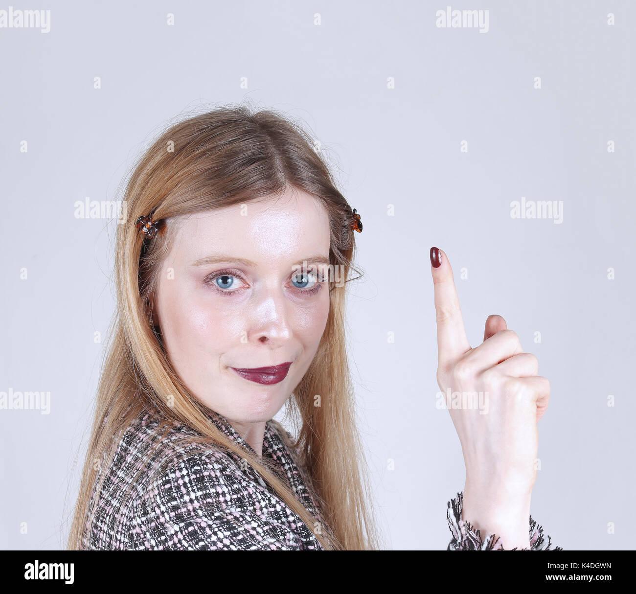 Mujer joven levantando el dedo índice haciendo un punto Imagen De Stock