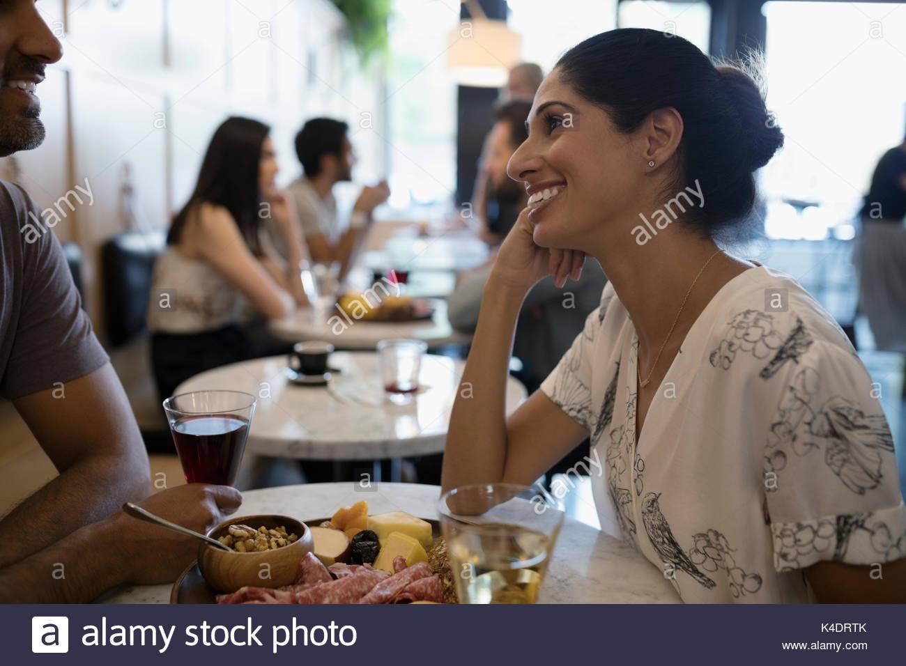Mujer sonriente al novio, comiendo y bebiendo vino en la mesita de café Imagen De Stock