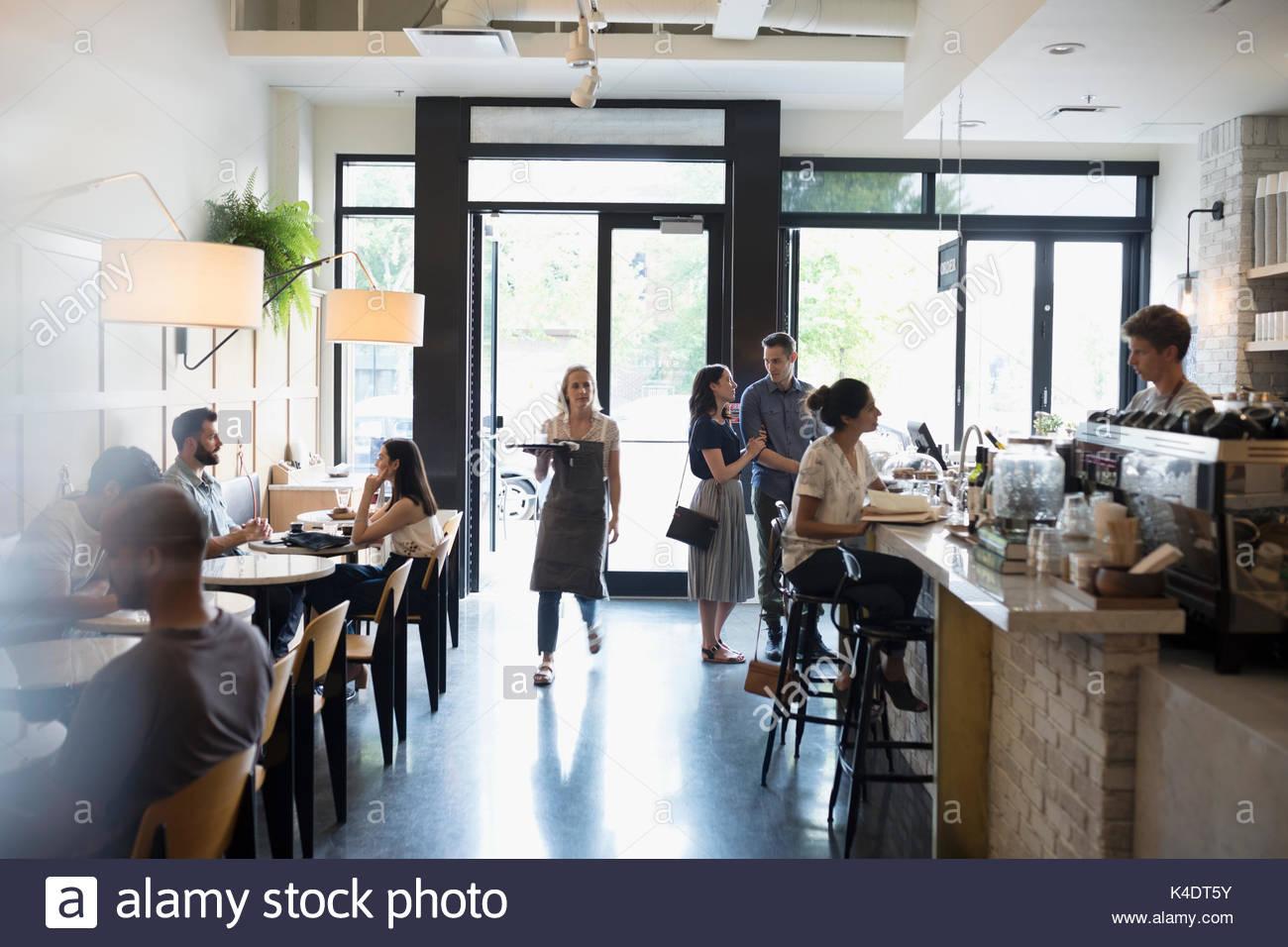Camarera y clientes en cafe Imagen De Stock