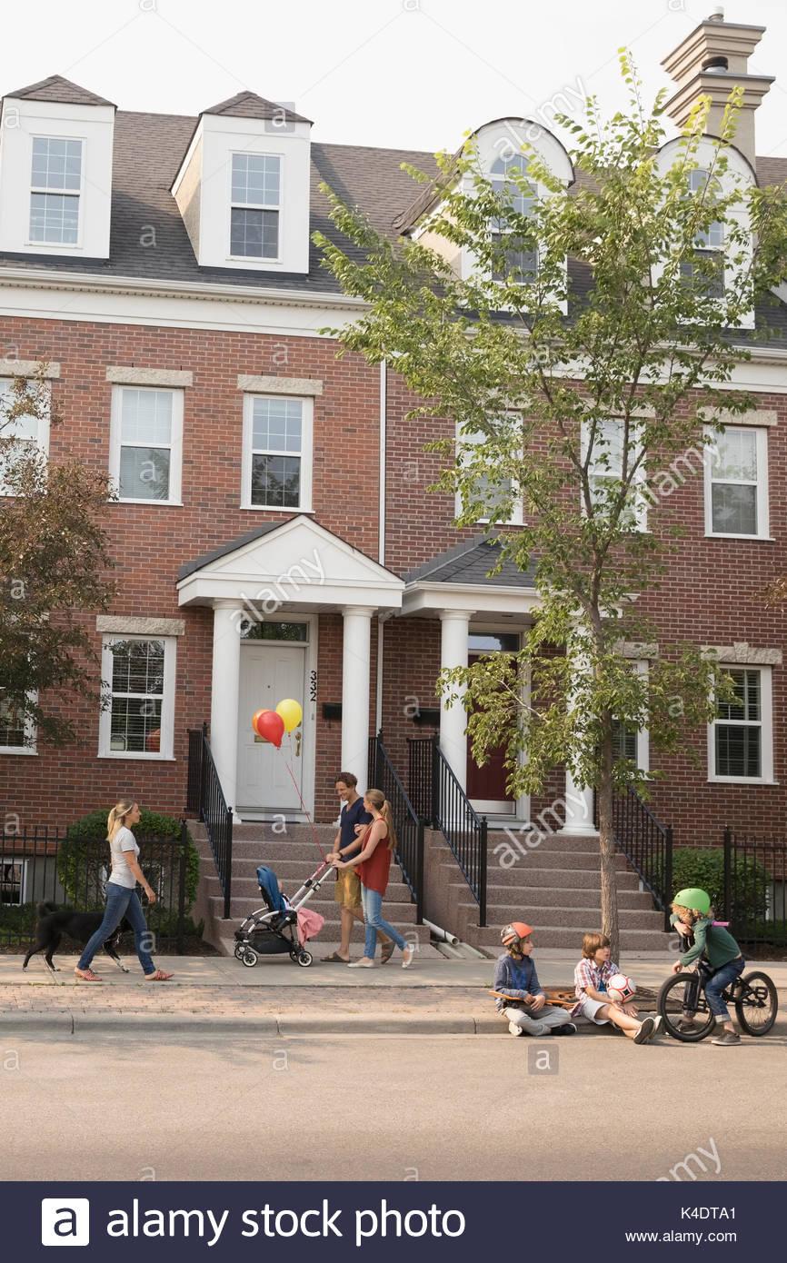 Familia, mujer joven con perros y niños con bicicleta en barrio acera Imagen De Stock