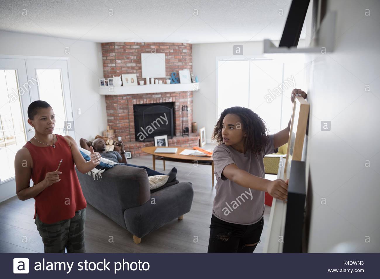 Madre e hija colgar marcos de fotos en el salón wall Foto & Imagen ...