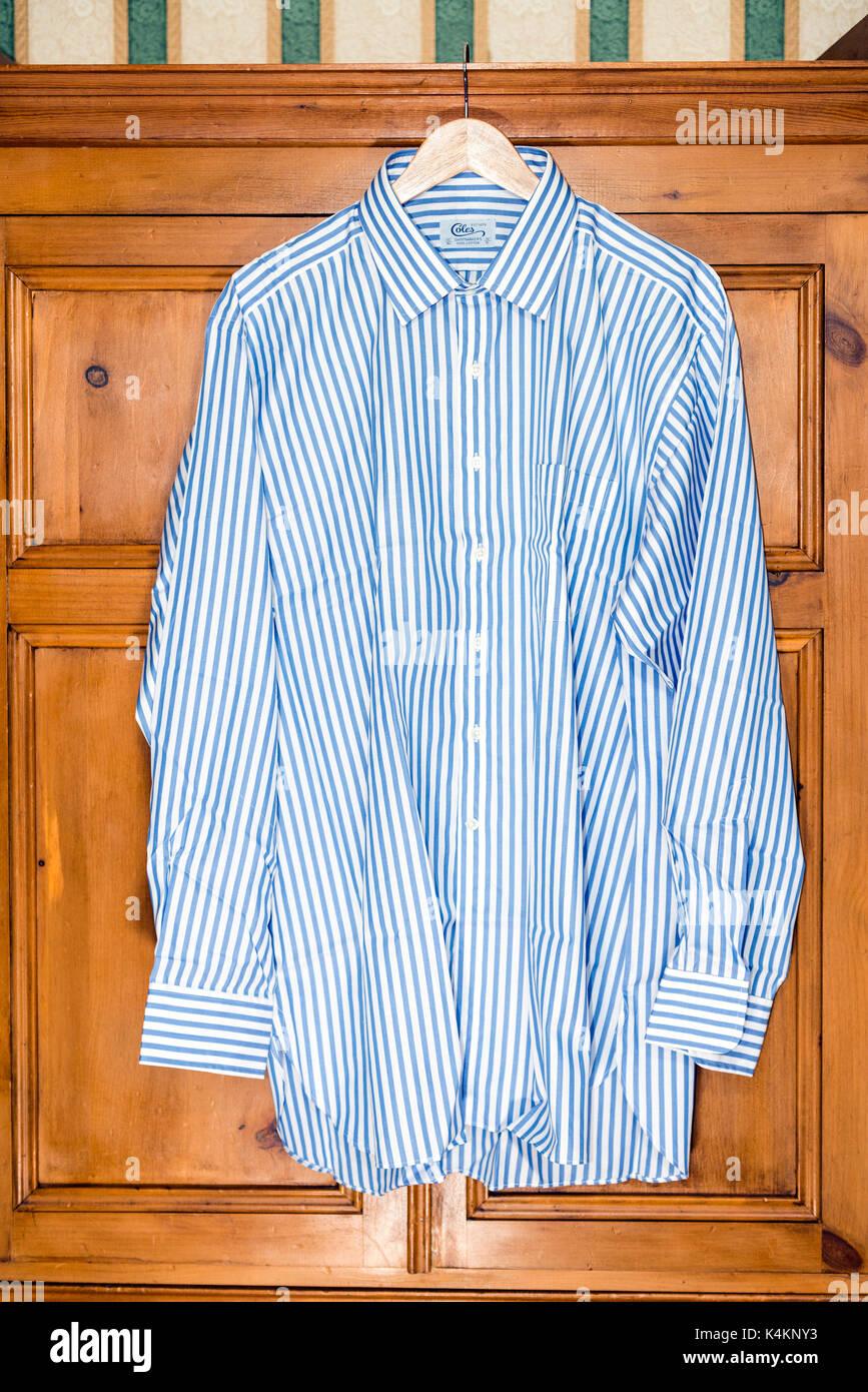Mans camiseta colgando en una percha en frente de un armario de pino, Reino Unido. Foto de stock