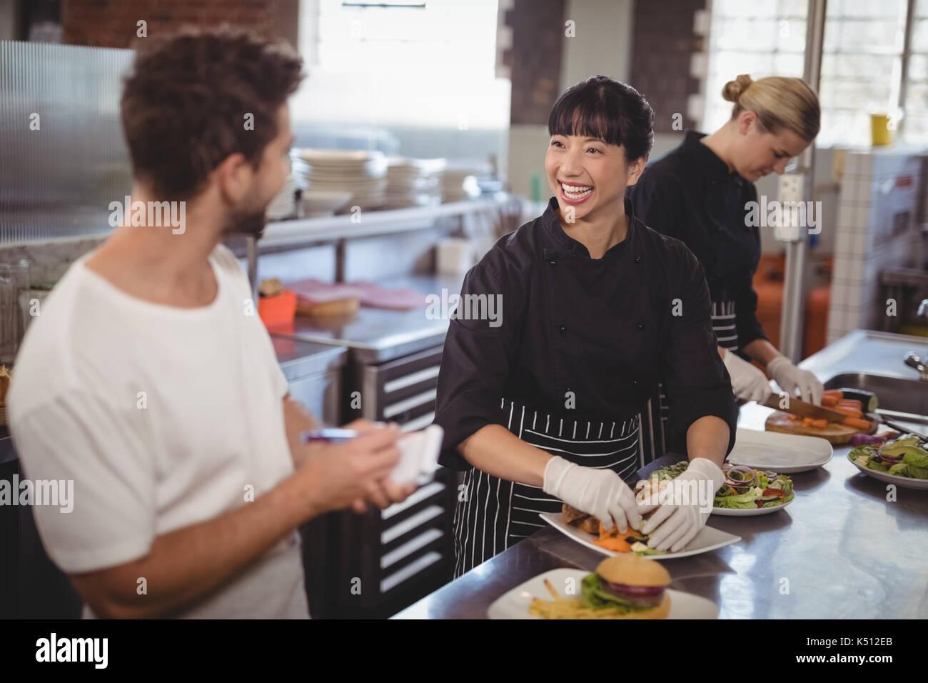 Alegre camarero y cocinero femenina trabaja en la cocina en el cafe Foto de stock
