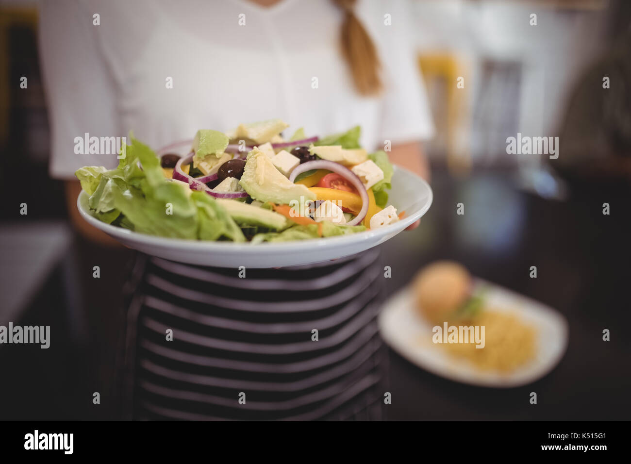 Sección media de la camarera mantiene fresca ensalada griega en la placa en el cafe Imagen De Stock