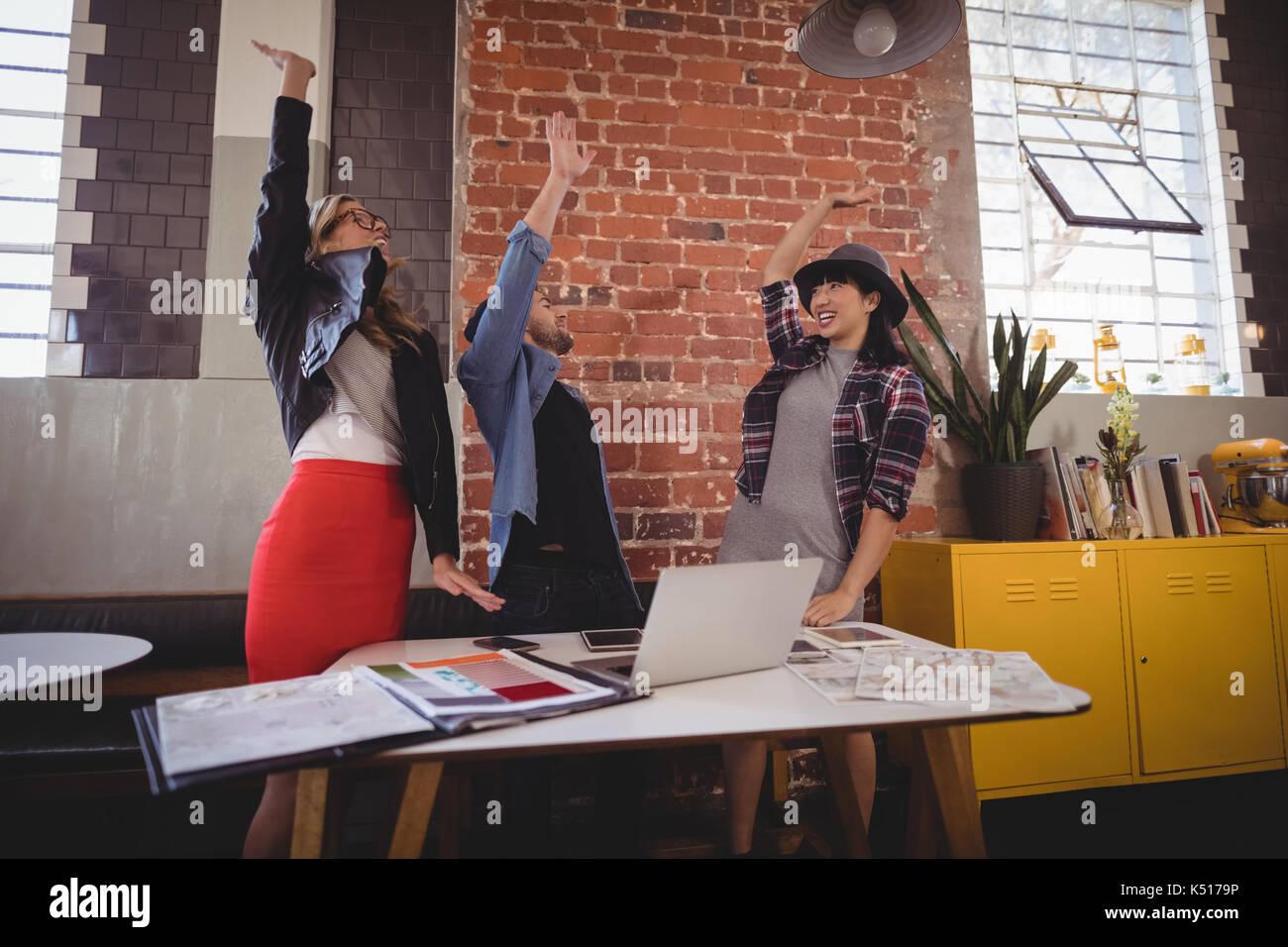 Emocionada joven equipo creativo de pie con los brazos levantados en la cafetería Imagen De Stock