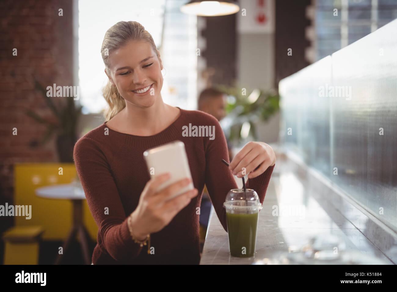 Sonriente joven mujer rubia utilizando el smartphone mientras está sentado en el mostrador con la bebida en la cafetería. Imagen De Stock