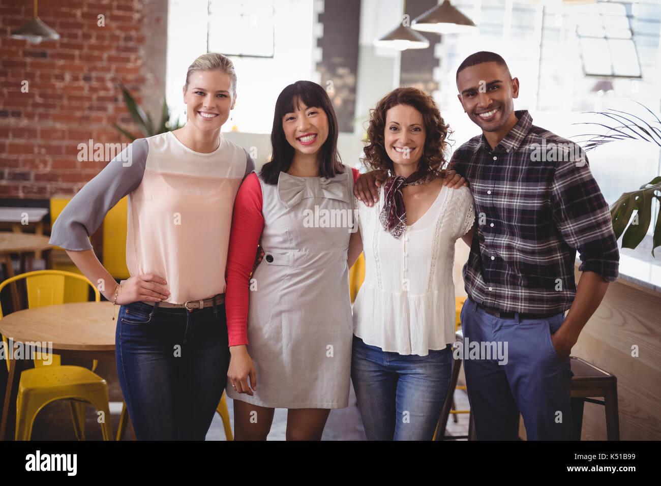 Retrato de sonriente joven amigos de pie con los brazos alrededor en la cafetería Imagen De Stock