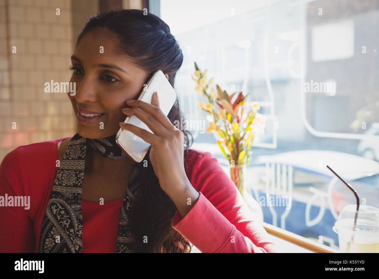 Mujer joven mirando a otro lado mientras habla por teléfono móvil en el cafe Imagen De Stock