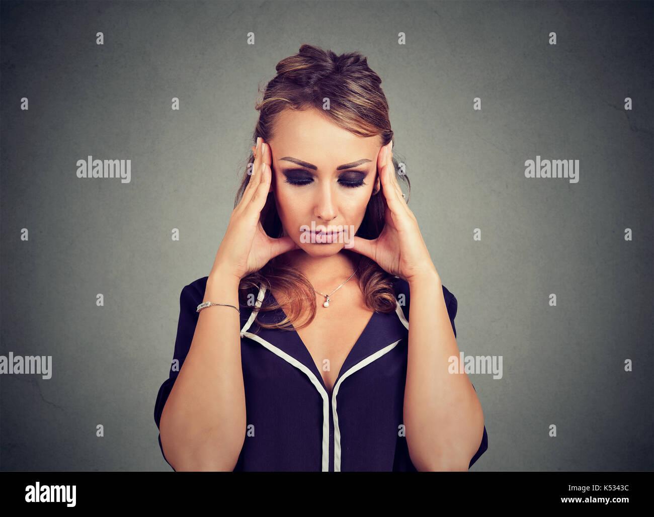 Closeup retrato triste mujer con expresión de cara destacó preocupados mirando hacia abajo Imagen De Stock