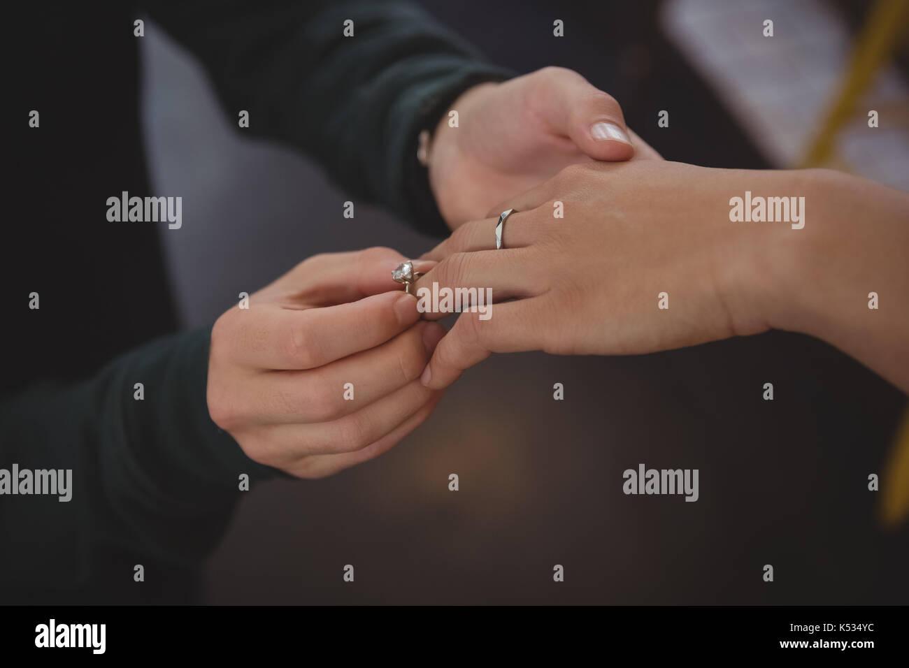 Imagen recortada del hombre colocando el anillo en el dedo de la mujer en el café Imagen De Stock