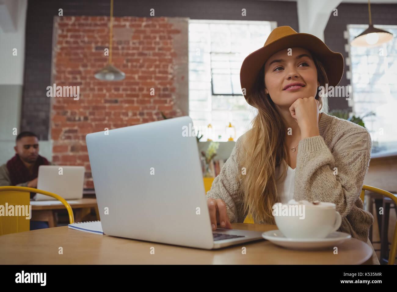 Pensativo joven con laptop apartar la mirada en el café Imagen De Stock