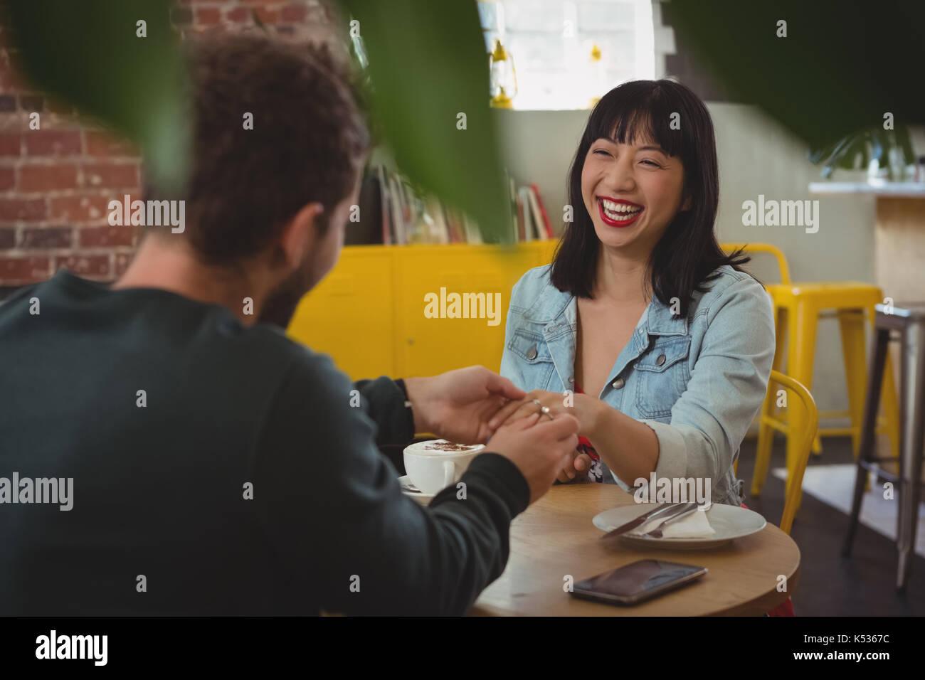 Hombre haciendo ring en la feliz joven dedo en el cafe Imagen De Stock