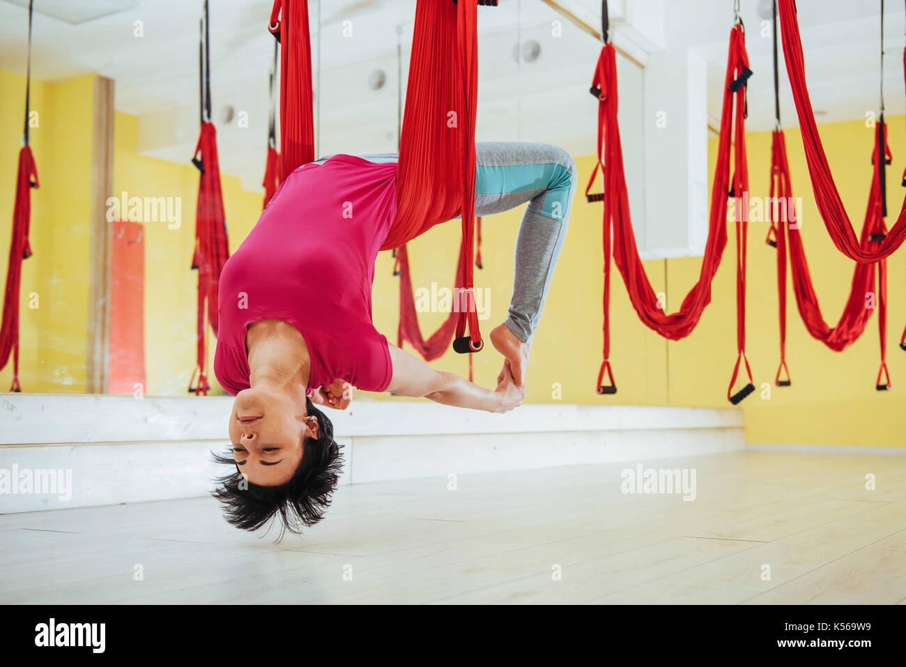 Hermosa mujer joven practicando yoga volar con una hamaca en la Bright Studio. el concepto de la salud física y Foto de stock