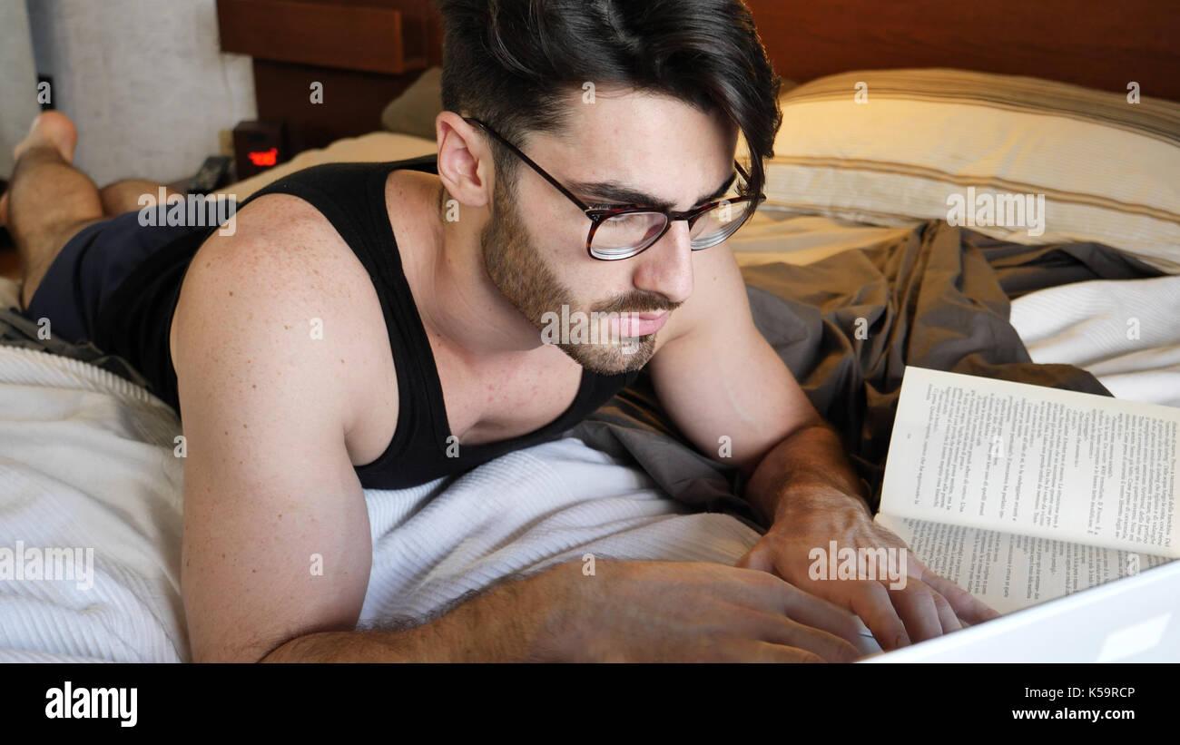 El hombre estudiando en la cama Imagen De Stock