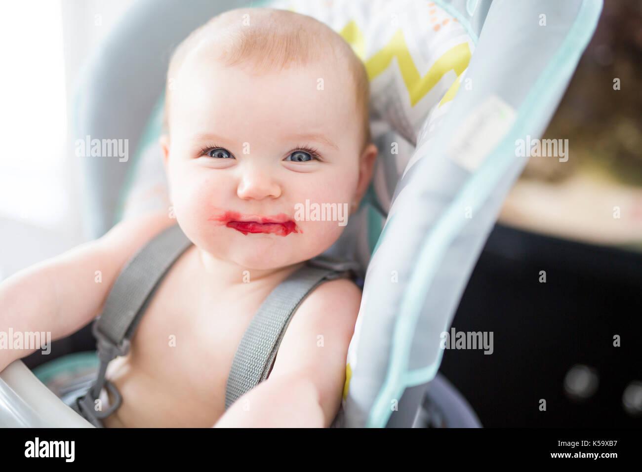 Niña sentada en la silla alta para comer Imagen De Stock