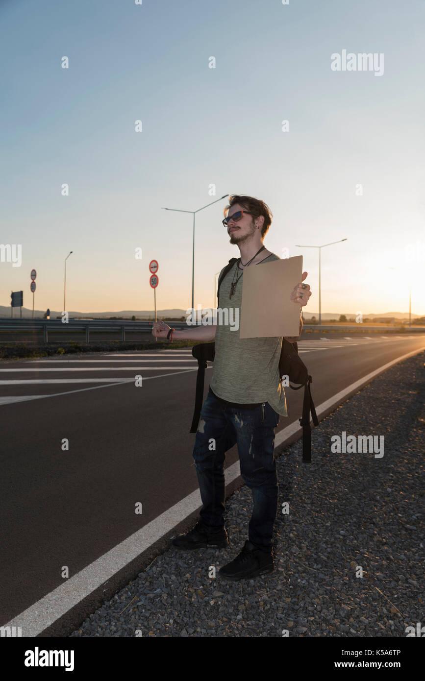 Hombre de 21 años en una autopista hitchhikikng Foto de stock