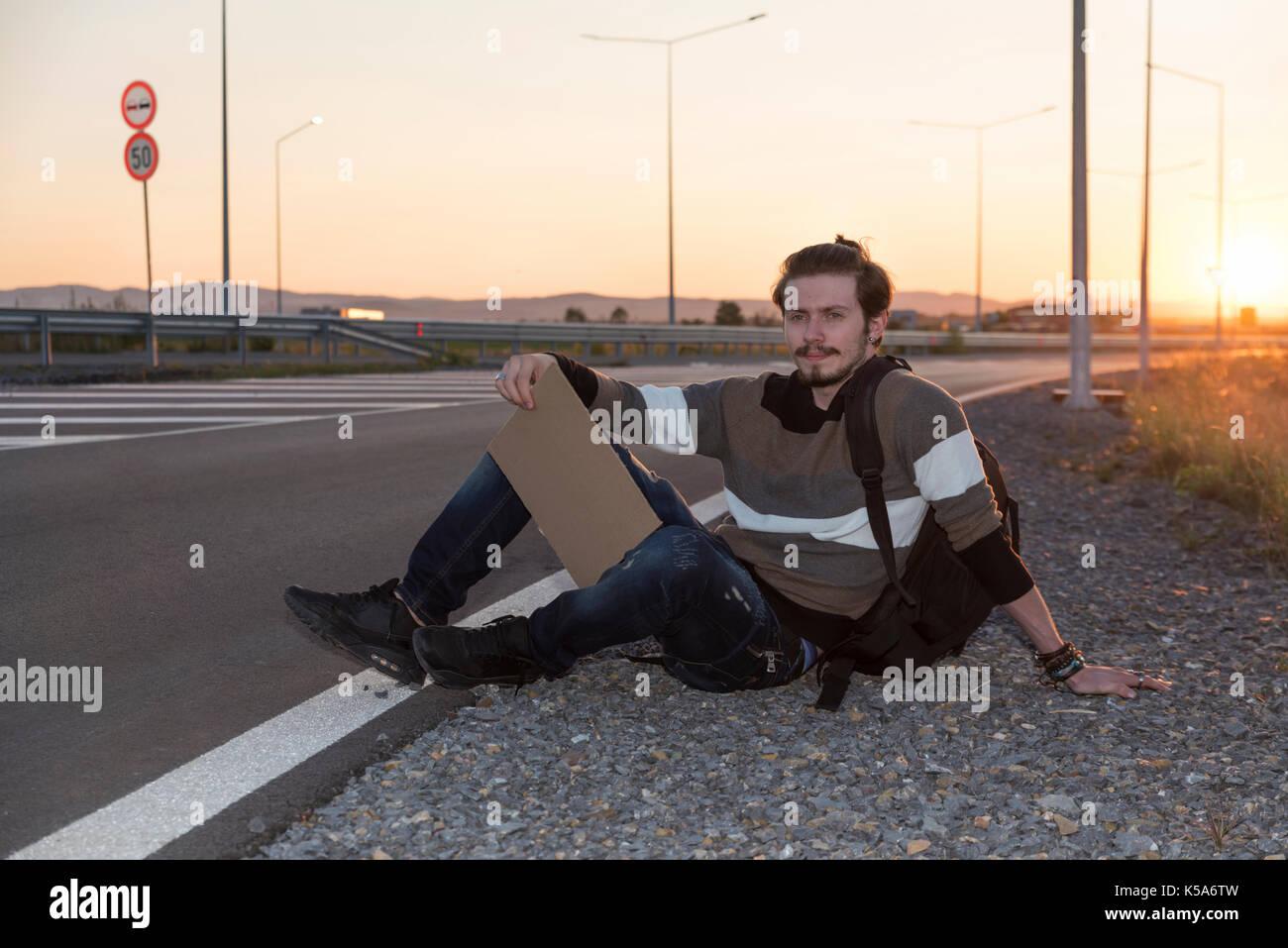 Hombre de 21 años de edad, sentada en el suelo y hitchhikikng Foto de stock